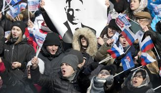 People sing Russian national anthem during a massive rally in support of Russian President and presidential candidate Vladimir Putin, at the Luzhniki stadium in Moscow, Russia, Saturday, March 3, 2018. Two weeks before the Russian presidential election, tens of thousands of Vladimir Putin's supporters gathered for a rally at Moscow's sprawling main sports complex. (AP Photo/Pavel Golovkin)