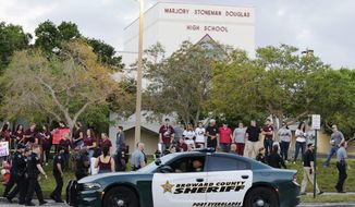 In this Feb. 28, 2018, file photo, a police car drives by Marjory Stoneman Douglas High School in Parkland, Fla., as students returned to class for the first time since a former student opened fire there with an assault weapon. (AP Photo/Terry Renna)