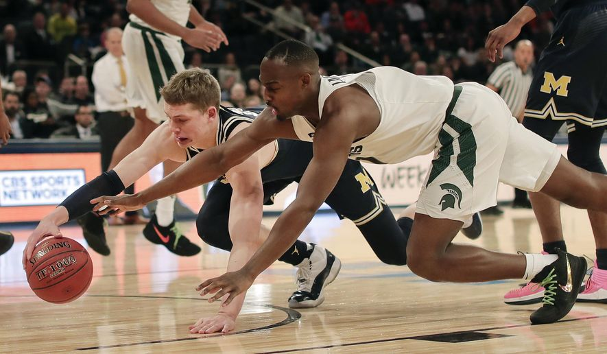 Michigan forward Moritz Wagner, left, of Germany, and Michigan State guard Joshua Langford (1) dive for a loose ball during the first half of an NCAA college basketball game in the semifinals of the Big Ten Conference tournament, Saturday, March 3, 2018, in New York. (AP Photo/Julie Jacobson)