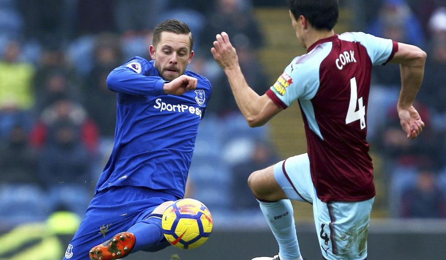 Everton's Gylfi Sigurdsson, left, and Burnley's Jack Cork in action during their English Premier League soccer match at Turf Moor, Burnley, England, Saturday March 3, 2018. (Dave Thompson/PA via AP)