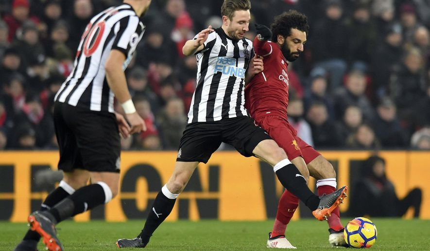Newcastle United's Paul Dummett, centre and Liverpool's Mohamed Salah, right, battle for the ball, during the English Premier League soccer match between Liverpool and Newcastle United, at Anfield, in Liverpool, England, Saturday March 3, 2018. (Anthony Devlin/PA via AP)