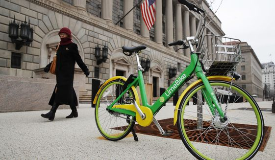 In this Feb. 13, 2018 photo, a woman walks past a dockless bike parked outside of the Commerce Department in Washington. Shared bikes that can be left wherever the rider ends up are helping more people get access to the mode of transportation that reduces car traffic and increases exercise. But the dockless bikes are also producing some chaos with discarded bikes cluttering public spaces, blocking sidewalks and even placed in trees and lakes. Over the last year, startup companies have brought the bikes that don't require docking stations into city after city in the U.S. (AP Photo/Jacquelyn Martin)