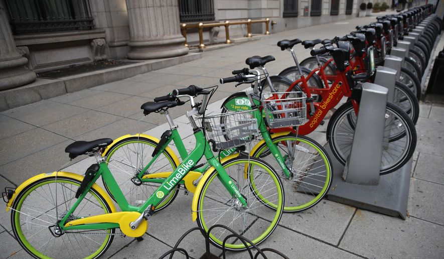 In this Feb. 13, 2018, file photo, two dockless LimeBike's share the sidewalk with others from Washington, D.C.'s docked share program called Capital Bikeshare in Washington. (AP Photo/Jacquelyn Martin) ** FILE **