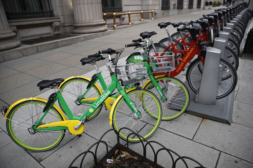 In this Feb. 13, 2018 photo, two dockless LimeBike's share the sidewalk with others from Washington, D.C.'s docked share program called Capital Bikeshare in Washington. Shared bikes that can be left wherever the rider ends up are helping more people get access to the mode of transportation that reduces car traffic and increases exercise. But the dockless bikes are also producing some chaos with discarded bikes cluttering public spaces, blocking sidewalks and even placed in trees and lakes. Over the last year, startup companies have brought the bikes that don't require docking stations into city after city in the U.S. (AP Photo/Jacquelyn Martin) **FILE**