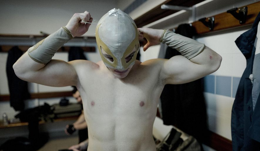 In this photo dated Saturday, Feb. 24, 2018, wrestler Ace Angel ties his mask before taking part in a wrestling charity gala in Ivry-sur-Seine, south of Paris, France. With revolutionary slogans and a message of support for the unemployed, this was no ordinary wrestling match. (AP Photo/Kamil Zihnioglu)