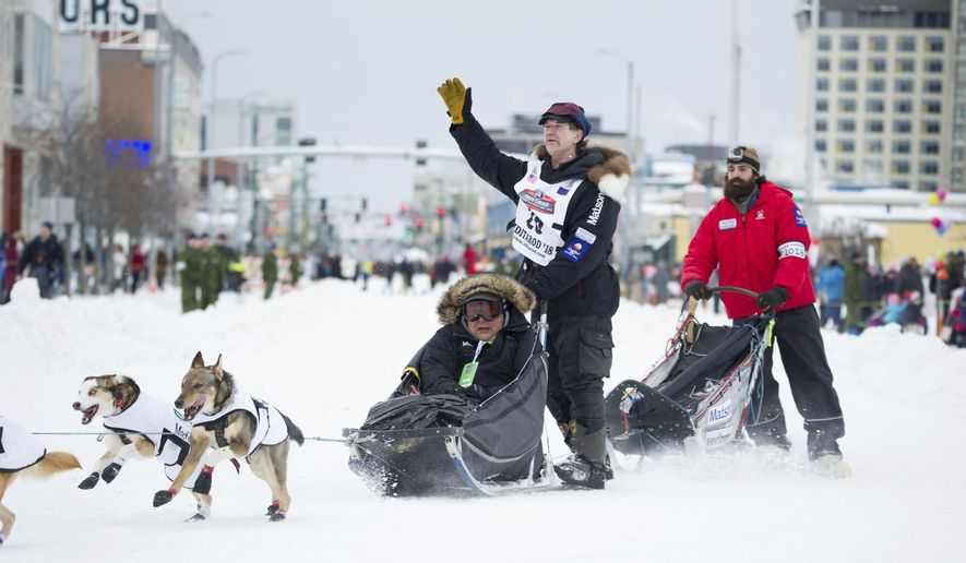 Iditarod musher Allen Moore waves to the crowd during the ceremonial start of the Iditarod Trail Sled Dog Race, Saturday, March 3, 2018, in Anchorage, Alaska. Moore has just won the Yukon Quest, a dog sled race from Whitehorse, Yukon Territory to Fairbanks, Alaska. (AP Photo/Michael Dinneen)