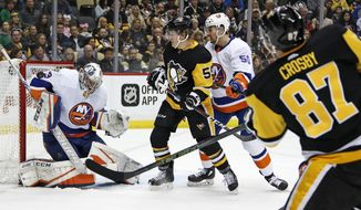 New York Islanders goaltender Christopher Gibson (33) stops a shot by Pittsburgh Penguins' Sidney Crosby (87) in the second period of an NHL hockey game in Pittsburgh, Saturday, March 3, 2018. Penguins' Jake Guentzel (59) looks for a rebound with Islanders' Adam Pelech (50) defending. (AP Photo/Gene J. Puskar)