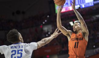 Florida guard Chris Chiozza (11) puts up a shot over Kentucky forward PJ Washington (25) during the first half of an NCAA college basketball game in Gainesville, Fla., Saturday, March 3, 2018. (AP Photo/Ron Irby)