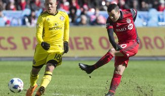 Toronto FC's Sebastian Giovinco , right, gets a shot away past Columbus Crew defender Cristian Martinez during the first half of an MLS soccer game in Toronto on Saturday, March 3, 2018. (Chris Young/The Canadian Press via AP)