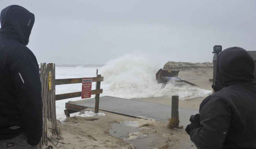 Orleans Natural Resource manager Nate Sears, left, and Ed Hathorne keep an eye on the high tide surf at Nauset Beach, Saturday, March 3, 2018. (Steve Heaslip/Cape Cod Times via AP)