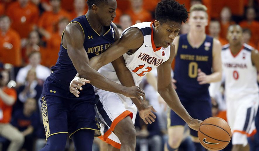 Virginia guard De'Andre Hunter (12) is fouled by Notre Dame forward Juwan Durham (11) during the second half of an NCAA college basketball game in Charlottesville, Va., Saturday, March 3, 2018. Virginia won the game 62-57. (AP Photo/Steve Helber)