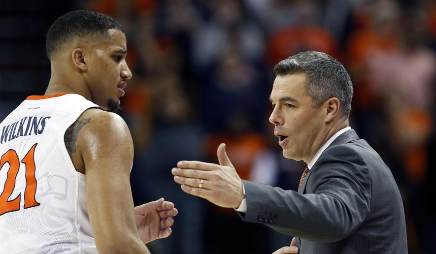 Virginia forward Isaiah Wilkins (21) talks with head coach Tony Bennett during the first half of an NCAA college basketball game against Notre Dame in Charlottesville, Va., Saturday, March 3, 2018. (AP Photo/Steve Helber) **File**