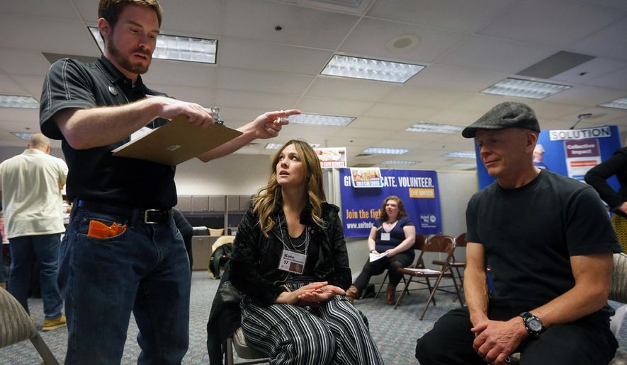 In this Wednesday, Feb. 28, 2018 photo, United Way's Christopher Mackey, left, role plays a police officer as he detains Erika Willis, middle, the executive director of Tumbleweed, and Steve Restad, a volunteer, for a simulated drug deal during the poverty simulation at United Way of Yellowstone County, Mont. Pretend money, families and events all played a role in a United Way of Yellowstone County simulation designed to offer insights into the lives of Americans struggling to get by. (Bethany Baker/The Billings Gazette via AP)