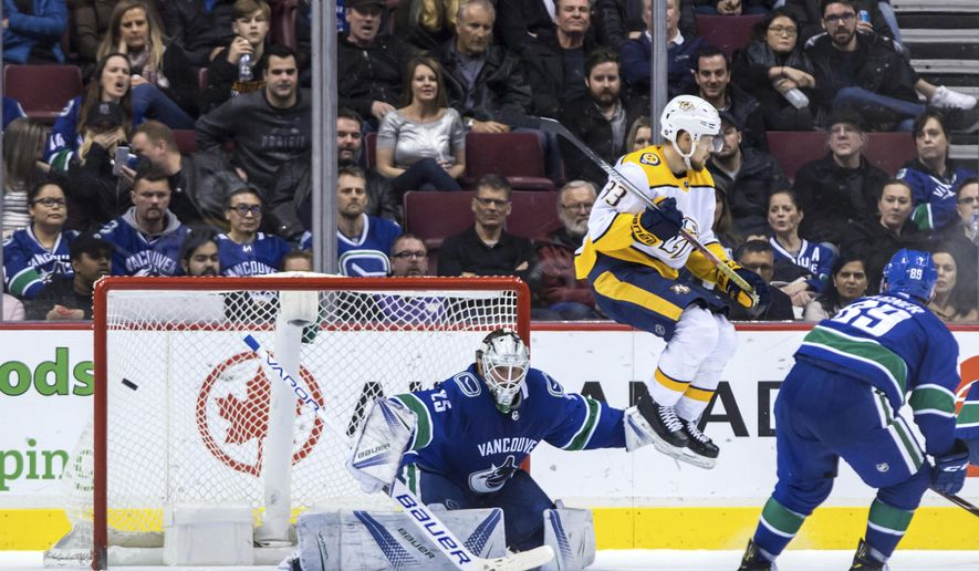 Nashville Predators' Viktor Arvidsson (33), of Sweden, jumps in front of goalie Vancouver Canucks goalie Jacob Markstrom, of Sweden, as Nashville's Calle Jarnkrok, not seen, scores the winning goal while Vancouver's Sam Gagner, right, watches during overtime in an NHL hockey game Friday, March 2, 2018, in Vancouver, British Columbia. (Darryl Dyck/The Canadian Press via AP)