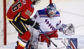 New York Rangers goalie Henrik Lundqvist, right, of Sweden, makes a save against Calgary Flames' Troy Brouwer during first-period NHL hockey game action in Calgary, Alberta, Friday, March 2, 2018. (Larry MacDougal/The Canadian Press via AP)