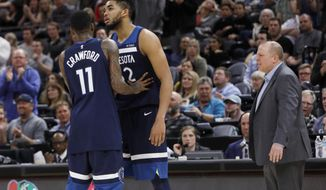 Minnesota Timberwolves' Karl-Anthony Towns, middle, is held back by Jamal Crawford (11) after he was called for his second technical foul, and was ejected during the first half of the team's NBA basketball game against the Utah Jazz on Friday, March 2, 2018, in Salt Lake City. (AP Photo/Kim Raff)