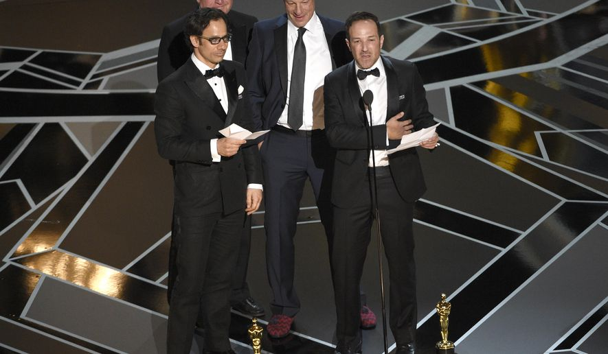 """Dan Cogan, from left, James R. Swartz, David Fialkow, and Bryan Fogel accept the award for best documentary feature for """"Icarus"""" at the Oscars on Sunday, March 4, 2018, at the Dolby Theatre in Los Angeles. (Photo by Chris Pizzello/Invision/AP)"""