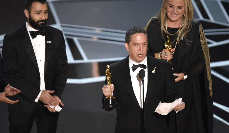 """Adrian Molina, from left, Lee Unkrich, and Darla K. Anderson accept the award for best animated feature film for """"Coco"""" at the Oscars on Sunday, March 4, 2018, at the Dolby Theatre in Los Angeles. (Photo by Chris Pizzello/Invision/AP)"""