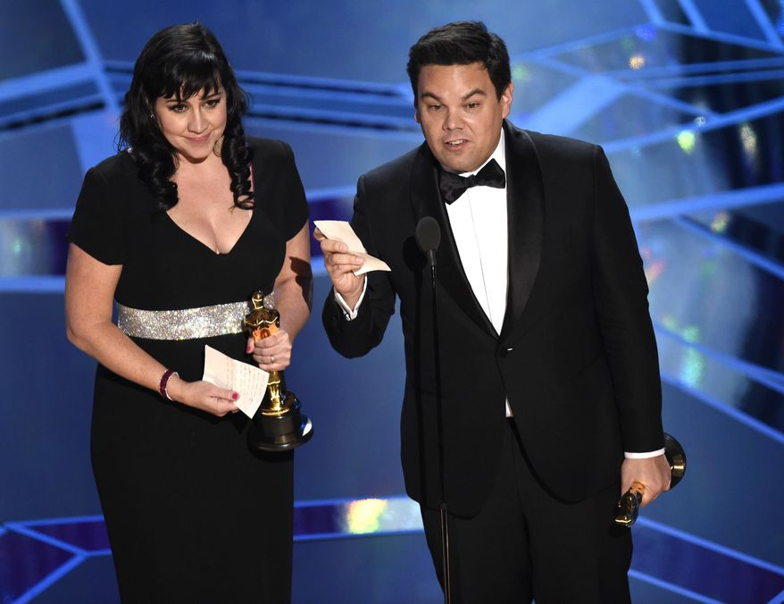 "Kristen Anderson-Lopez, left, and Robert Lopez accept the award for best original song for ""Remember Me"" from ""Coco"" at the Oscars on Sunday, March 4, 2018, at the Dolby Theatre in Los Angeles. (Photo by Chris Pizzello/Invision/AP)"