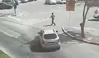 A Israeli-Arab man runs over Israeli soldier in Acre in northern Israel on Sunday. This is a screengrab from a video taken by a bystander outside the market where a border police officer was hit showed and the jeep being driven into the curb and hitting the officer.    (Courtesy of CCTV and The Jerusalem Post)