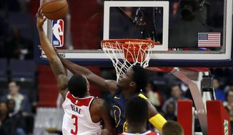 Washington Wizards guard Bradley Beal (3) is hit by Indiana Pacers guard Victor Oladipo (4) but does not get a foul call during the first half of an NBA basketball game Sunday, March 4, 2018, in Washington. (AP Photo/Alex Brandon)