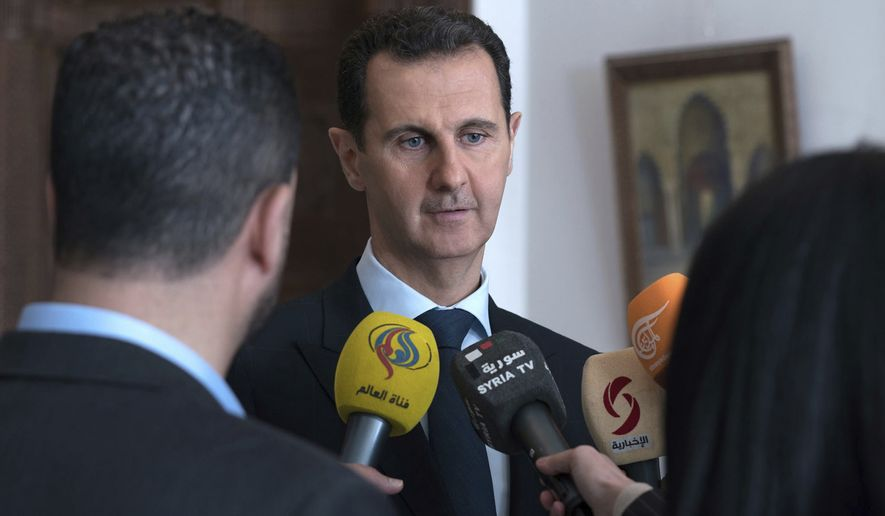 This photo provided by the official Facebook page of the Syrian Presidency, Syrian President Bashar Assad, center, speaks with reporters, in Damascus, Syria, Sunday, March 4, 2018. Assad vowed Sunday to continue with a military offensive in a rebel-held region near the capital, as troops and allied militias captured a number of villages and towns in the besieged region, in their largest advance since a wide-scale operation began last month. (Syrian Presidency Facebook Page via AP)