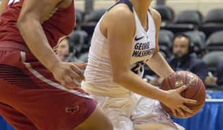 George Washington's Mei-Lyn Bautista (21) drives the lane for a basket with Saint Joseph's guard Chelsea Woods (32) in the lane during the first half of an NCAA college basketball game in the Atlantic-10 championship tournament in Richmond, Va., Sunday, March 4, 2018. (AP Photo/Matt Bell)