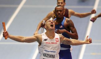 Poland's Jakub Krzewina celebrates after winning the gold medal in the men's 4x400-meter relay final at the World Athletics Indoor Championships in Birmingham, Britain, Sunday, March 4, 2018. (AP Photo/Alastair Grant)