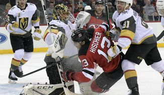 New Jersey Devils center Nico Hischier (13) is checked by Vegas Golden Knights center Jonathan Marchessault (81) into Golden Knights goaltender Marc-Andre Fleury (29) during the second period of an NHL hockey game Sunday, March 4, 2018, in Newark, N.J. (AP Photo/Bill Kostroun)
