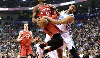Toronto Raptors forward C.J. Miles (0) collides with Charlotte Hornets guard Jeremy Lamb on his way to the basket during the first half of an NBA basketball game, Sunday, March 4, 2018, in Toronto. (Frank Gunn/The Canadian Press via AP)