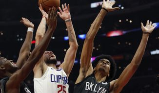 Los Angeles Clippers guard Austin Rivers, center, goes to the basket while defended by Brooklyn Nets guard Nik Stauskas, left, and center Jarrett Allen during the first half of an NBA basketball game, Sunday, March 4, 2018, in Los Angeles. (AP Photo/Ringo H.W. Chiu)