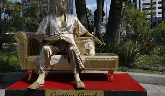 """A dog named """"Sassi"""" sits next to a golden statue of a bathrobe-clad Harvey Weinstein, seated atop a couch on the sidewalk along Hollywood Blvd., in Los Angeles Thursday, March 1, 2018. The piece, titled """"Casting Couch,"""" is a collaborative effort between a Los Angeles street artist known as Plastic Jesus and Joshua """"Ginger"""" Monroe, creator of the nude Donald Trump statue. Plastic Jesus said the piece was meant to shine a light on the entertainment industry's sexual misconduct crisis and the disgraced movie mogul's prominent role in it. (AP Photo/Damian Dovarganes)"""