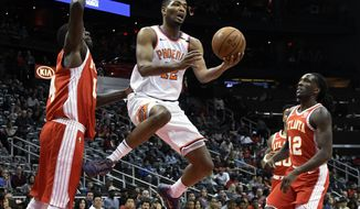 Phoenix Suns forward TJ Warren shoots while flanked by the defense of Atlanta Hawks center Dewayne Dedmon, left, and forward Taurean Prince (12) during the first half of an NBA basketball game Sunday, March 4, 2018, in Atlanta. (AP Photo/John Amis)