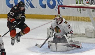 Anaheim Ducks defenseman Josh Manson (42) leaps as Chicago Blackhawks goalie Anton Forsberg (31) defends in the first period of an NHL hockey game in Anaheim, Calif., Sunday, March 4, 2018. (AP Photo/Reed Saxon)