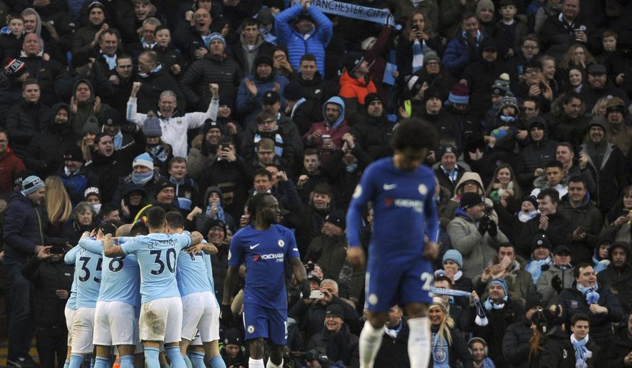 Manchester City's Bernardo Silva celebrates with his teammates after scoring his side's opening goal during the English Premier League soccer match between Manchester City and Chelsea at the Etihad Stadium in Manchester, England, Sunday, March 4, 2018. (AP Photo/Rui Vieira)