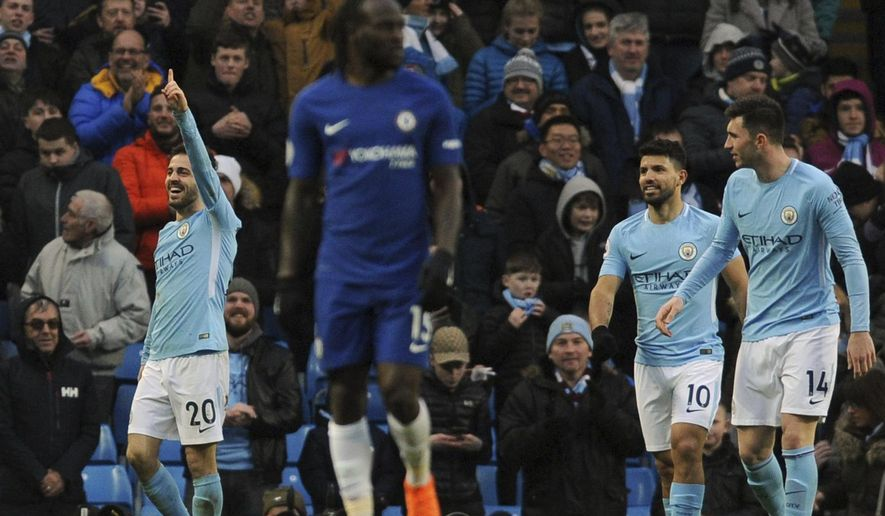 Manchester City's Bernardo Silva, left, celebrates after scoring his side's opening goal during the English Premier League soccer match between Manchester City and Chelsea at the Etihad Stadium in Manchester, England, Sunday, March 4, 2018. (AP Photo/Rui Vieira)