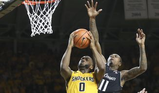 Wichita State forward Rashard Kelly goes to the basket against Cincinnati forward Gary Clark during the first half of a college basketball game on Sunday, March 4, 2018 in Wichita, Kan. (Travis Heying/The Wichita Eagle via AP)