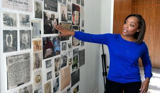"""In this Tuesday, Jan. 30, 2018 photo, Fawn Weaver points to a photo on a wall of a room covered with photographs and documents related to the beginnings of Jack Daniel's whiskey at her farmhouse in Lynchburg, Tenn. Weaver had come to Lynchburg to research the roots of a former slave named Nathan """"Nearest"""" Green, the man who some believed had taught the famous Jack Daniel to make whiskey more than 150 years ago (Shelley Mays /The Tennessean via AP)"""