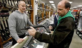 Wes Morosky, owner of Duke's Sport Shop. left, helps Ron Detka as he shops for a rifle on Friday, March 2, 2018, at his store in New Castle. Morosky said business has gone up recently, but that's thanks to the annual infusion of tax refund checks. Sales of firearms slowed dramatically after the election of President Donald Trump in 2016 allayed fears of a Democratic crackdown on gun owners. That trend continues, even with talk of gun control in Congress following the massacre of 17 people at a Florida high school last month. (AP Photo/Keith Srakocic)