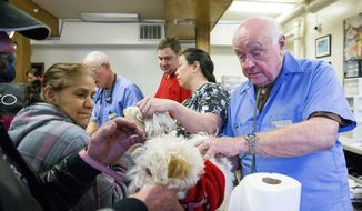 Dr. Stan Coe checks over Lola at the clinic. With help, Dr. Coe restarted the clinic in Dr. Bud Doney's honor, a veterinarian who started the clinic in 1985.  The clinic is free, the only requirement is that owners get their pets neutered after the first appointment. (Courtney Pedroza/The Seattle Times via AP)