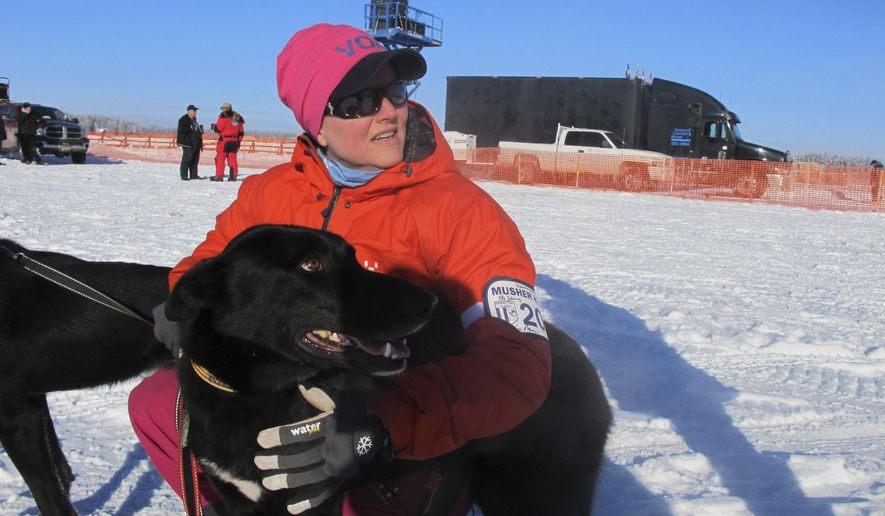 Handler Elin Bentsen poses with Hudson before the start of the Iditarod Trail Sled Dog Race in Anchorage, Alaska. Hudson bolted from his crate and was missing for about three hours Saturday during the ceremonial start in Anchorage. Musher Lars Monsen said he took the team to the last known spot where Hudson was seen Saturday, and Hudson either heard or smelled his pack and came back. (AP Photo/Mark Thiessen)