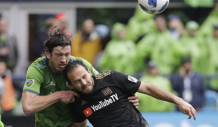 Seattle Sounders defender Gustav Svensson, left, heads the ball away from Los Angeles forward Marco Urena during the second half of an MLS soccer match, Sunday, March 4, 2018, in Seattle. Los Angeles won 1-0. (AP Photo/Ted S. Warren)