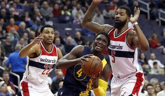 Indiana Pacers guard Victor Oladipo (4) drives between Washington Wizards forwards Otto Porter Jr. (22) and Markieff Morris (5) during the first half of an NBA basketball game Sunday, March 4, 2018, in Washington. (AP Photo/Alex Brandon)
