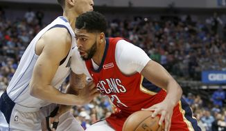 New Orleans Pelicans forward Anthony Davis, right, drives around Dallas Mavericks center Dwight Powell during the first half of an NBA basketball game on Sunday, March 4, 2018, in Dallas. (AP Photo/Brad Loper)