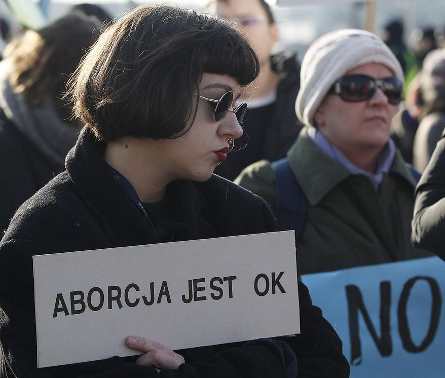"""Some 2,000 women march through downtown in Warsaw, Poland, Sunday, March 4, 2018 in the annual feminist """"Manifa"""" march held to mark International Women's Day and campaign for women's rights. Poster reads : Abortion is OK. (AP Photo/Czarek Sokolowski)"""