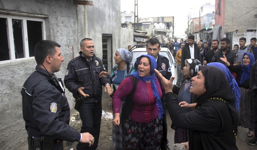 FILE - In this file photo dated Feb. 11, 2018, angry people try to stone the house of a man suspected of raping a 4-year-old girl, in Adana, southern Turkey, narrowly escaping the neighbourhood lynching attempt. The incident sparked a public outcry and calls for the government to increase the punishment of child sexual abuse offenders to include life sentences and chemical castration.(DHA-Depo Photos via AP, File)