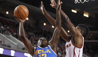 UCLA guard Kris Wilkes, left, shoots as Southern California forward Chimezie Metu defends during the first half of an NCAA college basketball game, Saturday, March 3, 2018, in Los Angeles. (AP Photo/Mark J. Terrill)