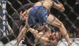 Brian Ortega, top, finishes off Frankie Edgar with a series of punches during their featherweight mixed martial arts bout at UFC 222 on Saturday, March 3, 2018, in Las Vegas. (Benjamin Hager/Las Vegas Review-Journal via AP)