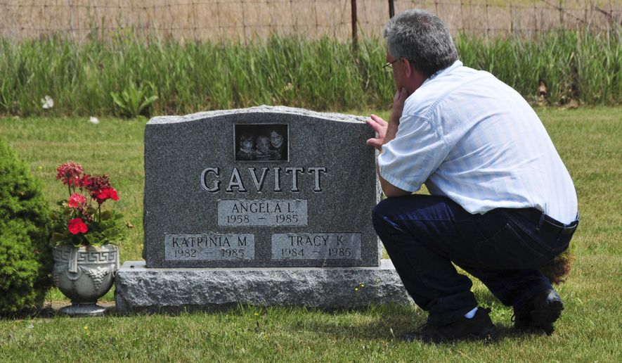In this June 6, 2012 photo provided by John Masson, David Gavitt visits the grave of his wife and two daughters in Ionia County, Mich., immediately after he was released from prison after 26 years. Gavitt was convicted of arson and murder in their 1985 deaths, but the convictions were overturned after scientists took a new look at evidence from the house fire. Gavitt now is seeking compensation under a Michigan law that pays people who were wrongly convicted. (John Masson via AP)