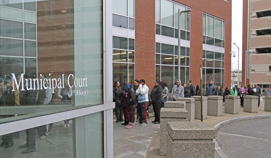 The line of people stretches outside the Public Safety building in Providence, R.I., Monday, March 5, 2018. The Rhode Island court was flooded with people contesting speeding tickets Monday after a new school zone speed camera program resulted in 12,000 tickets in 33 days. (Steve Szydlowski/Providence Journal via AP)